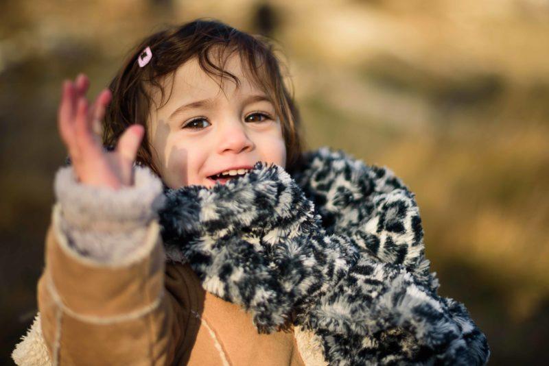 bébé heureux qui dit bonjour de la main