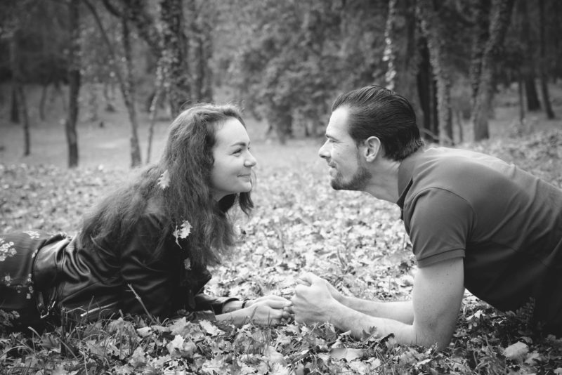 Couple d'amoureux couchés dans l'herbe qui se regardent