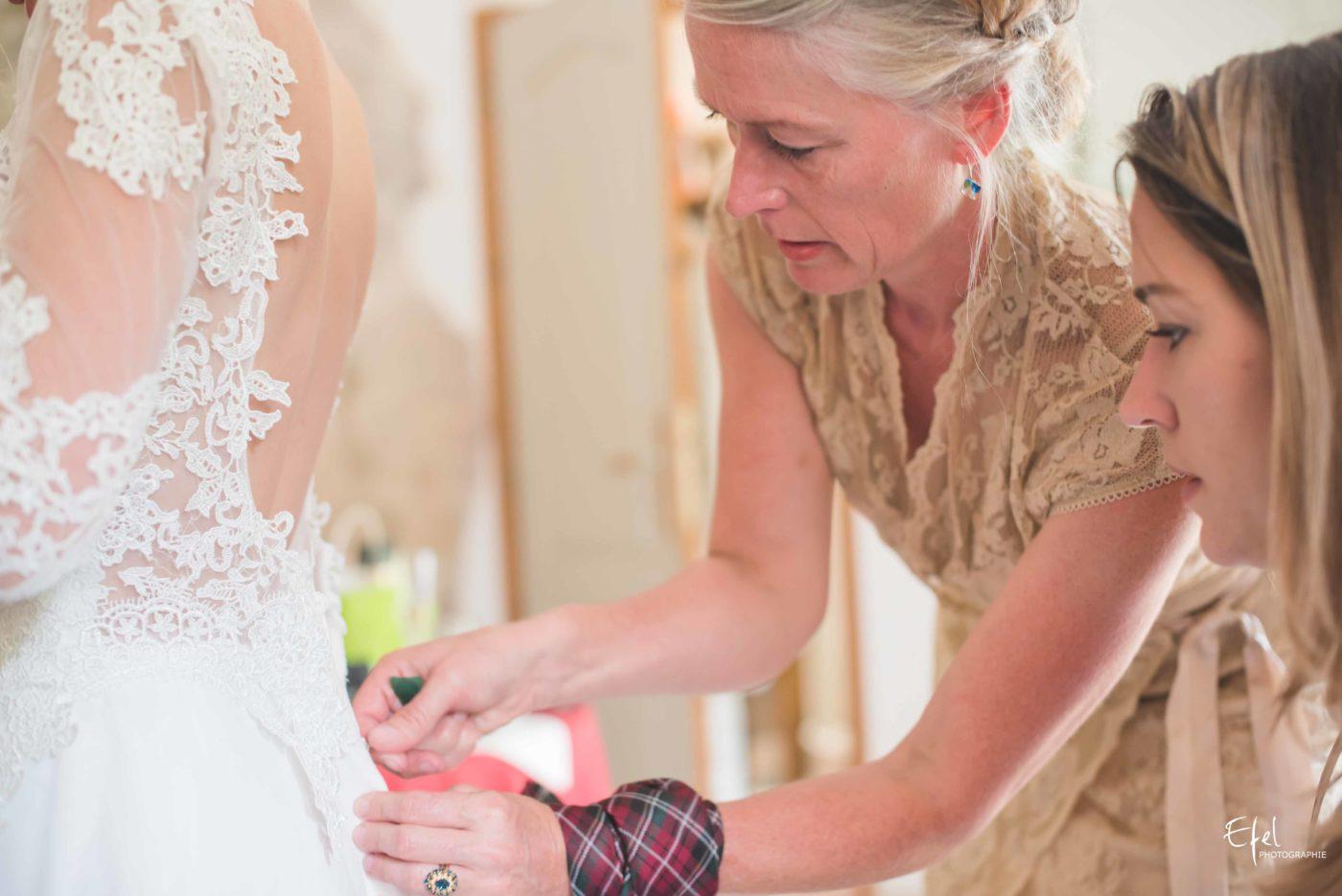 La mère de la mariée ferme la robe de sa fille - reportage de mariage alpes-maritimes