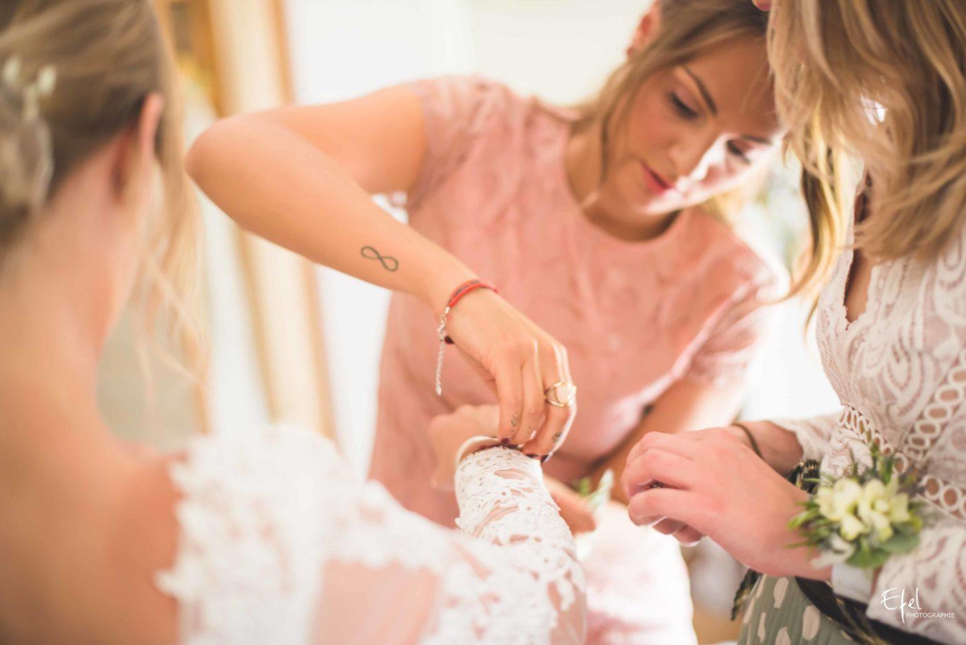 Le témoin de la mariée lui ajoute un bracelet décoratif avec une fleur